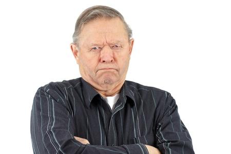 Senior man met gekruiste armen zag er erg chagrijnig, ongelukkig of boos.