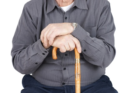 hip pain: Great detail shot of senior man or elderly sitted and leaning on his cane, focus on hands.