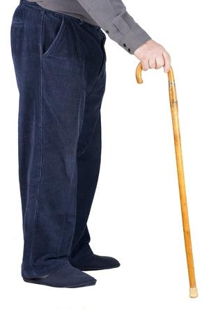 Profiel van de onderste helft van een oude man of een ouder iemand lopen met een houten stok, gekleed in een blauwe corduroy en slippers, geïsoleerd op wit.