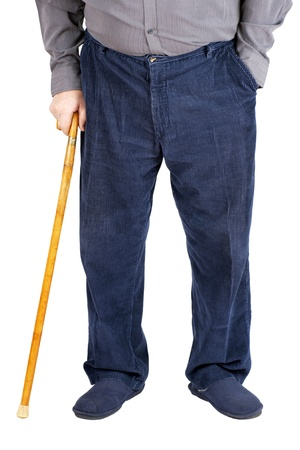 Bottom half of an old man or elderly person walking with a wood cane, wearing and blue corduroy and slippers, isolated on white. photo