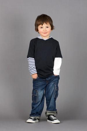 Cute niño en edad preescolar y de la cadera poco con grandes ojos marrones sonriendo con las manos en los bolsillos de los pantalones vaqueros sobre fondo gris.