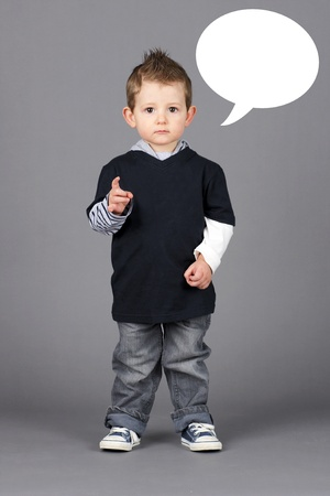 Cute and hip little toddler boy pointing at camera with a serious look on his face over grey background with white speech bubble easy to remove. photo