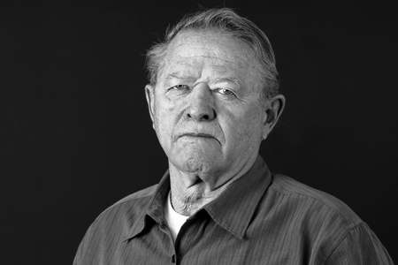 Dramatic black and white portrait of a senior man looking very serious, sad or depressed looking at camera,great facial details, shot in studio over black. photo