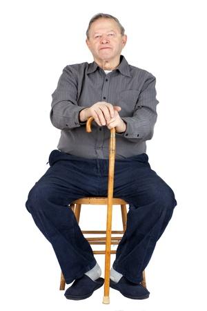 Senior of oude man zitten op oude houten stoel met zijn wandelstok om te rusten, gekleed in een blauwe corduroy en slippers, geïsoleerd op wit. Stockfoto