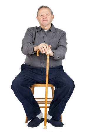 Senior or old man sitting down on old wooden chair with his cane to rest, wearing blue corduroy and slippers, isolated on white. photo
