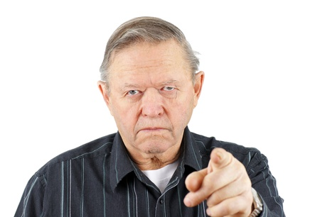 Grumpy angry senior or old man pointing his finger at the camera with a big frown on his face, blaming or warning you.