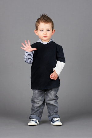 Cute and hip little boy wearing jeans and running shoes waving hello or showing fingers to count, shot in studio over grey background.