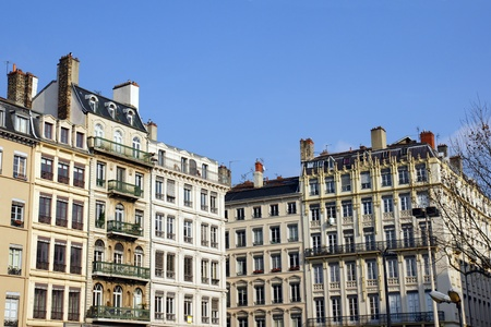 Typical old european stone building architecture of a busy city street with numerous apartments or flats and carved details on the facade, Lyon, France. photo