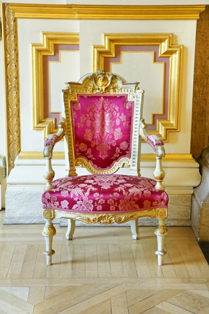 castle conditioning: Beautiful rich and luxurious old vintage antique pink silk chair with gold frame showing the wears and tears of years of service.
