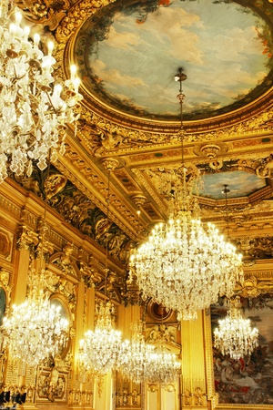 Opulent cristal chandeliers and gold leaves wood carved and painted ceiling, part of a french historical building, Lyon, France.