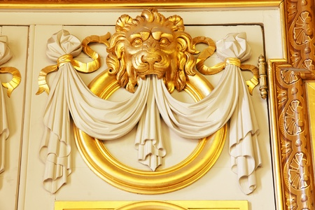 Great architectural detail above a door of an old european historical building of an ornate sculpted gold lion head.