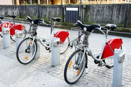 servicios publicos: El transporte alternativo: Bicicletas de alquiler estacionados en una estaci�n frente a muro de hormig�n en la ciudad de la antigua Europa. Foto de archivo