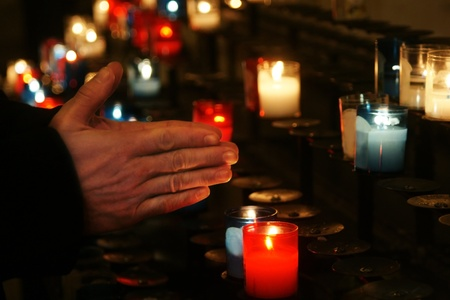 memorial candle: Religion concept: Praying hands in front of a series of colorful glass church candle at a place of worship; soft candlelight lighting. Stock Photo