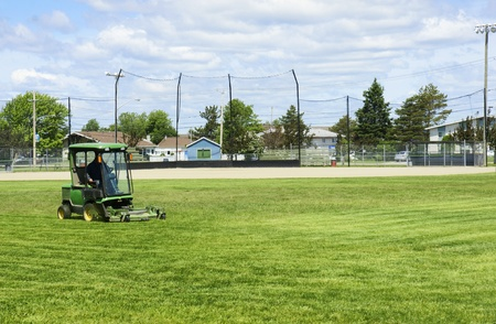 cut grass: Small tractor cutting the grass of the baseball playing field before the game.
