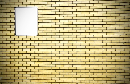 vignette: Dramatic vignette yellow brick wall background with blank white metal sign ready for your text. Stock Photo