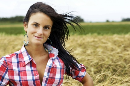Beautiful young woman or cowgirl with dark hair floating in the wind on a beautiful day in the wheat field photo