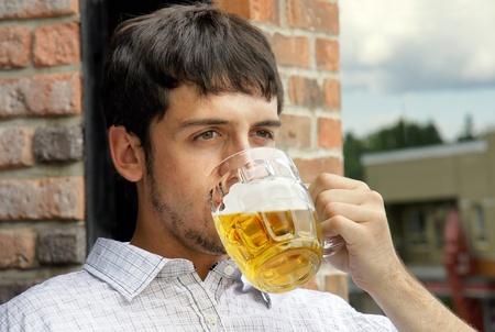 man drinkt bier: Portret van een trieste jonge man drinkt bier uit glas bok op de openlucht cafe's terras.