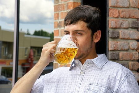 Young man drinking beer in glass bock, could be student or alcoholic. photo