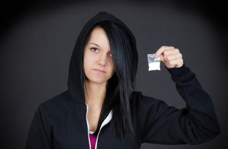 druggie: Cupo ritratto di una giovane donna tossicodipendente o adolescente col volto triste che mostra il suo sacchetto di droga.