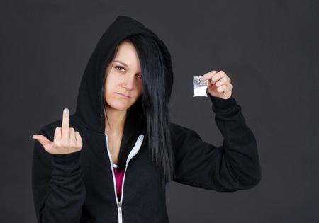druggie: Giovane tossicodipendente donna o rivenditore che mostra un pacchetto di droga e givng lo spettatore il dito. Archivio Fotografico