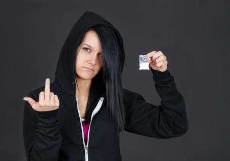 drogadicto: Joven adicto a las drogas o al distribuidor mujer mostrando un paquete de drogas y givng el espectador el dedo. Foto de archivo