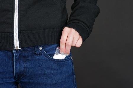 druggie: Donne droga pacchetto mano recuperando la nostra di tasca blue jeans con copia spazio su fondo nero.