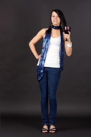 Complete body shot of a pretty young woman partying,  holding purple glass and toasting  photo