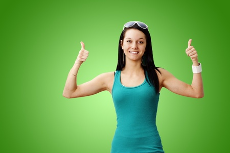 Pretty healthy and lean young woman smiling giving two thumbs up over gradient green background  perfect for weight loss or other achievement  Stock Photo - 12854127