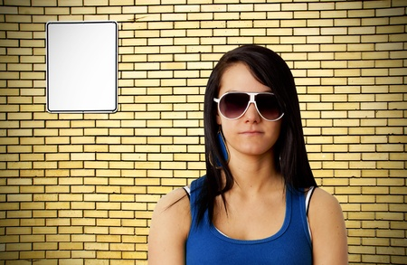 Tough looking young woman with sunglasses in front of yellow brick wall background with blank white metal sign ready for your text. photo