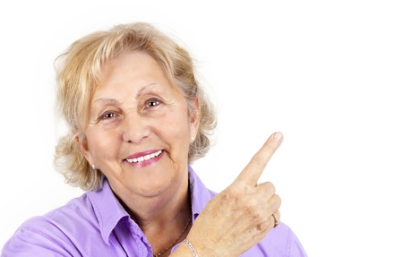 Beautiful senior woman smiling and pointing with her finger at blank space beside her, perfect ofr advertisement. Stock Photo - 12854990