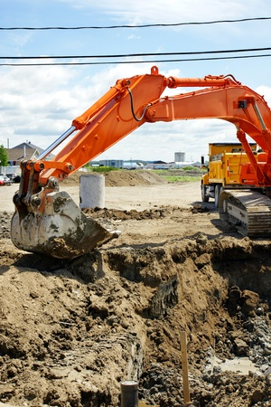 sewer: Construction: Bright orange mechanical digger removing dirt to install sewage and water line for a new neighborhood in rural North America with yellow dump truck behind it.