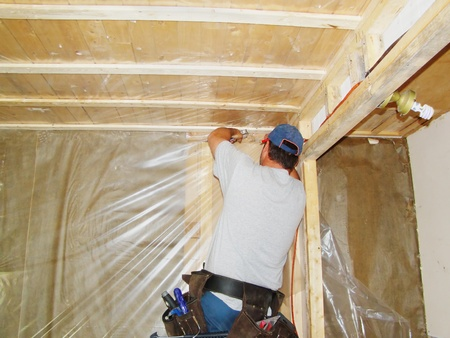Construction concept: man stapling plastic vapor barrier to isolate walls and ceiling of a house under major renovations. Banque d'images