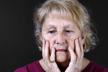 Dramatic portrait of a sad, depressed or worried senior woman with hands in her face, studio shot over black background.