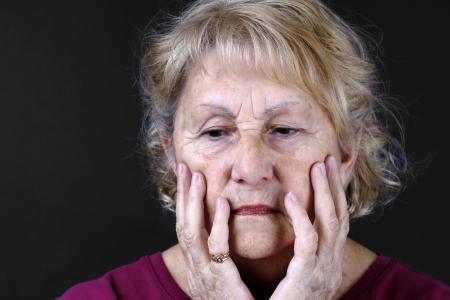 mourn: Ritratto drammatico di una triste, depresso o preoccupato donna anziano con le mani in viso, girato in studio su sfondo nero.