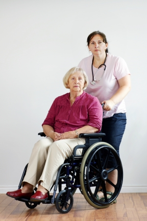 Senior woman in wheelchair at nursing home with middle-age nurse or aid. photo