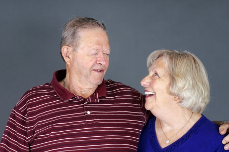 couple laughing: Happy senior couple laughing together, studio shot over grey background.