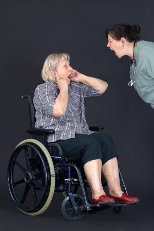 maltrato: Concepto de maltrato a personas mayores con una mujer mayor en una silla de ruedas llorando y tap�ndose los o�dos como una enfermera de mediana edad o un trabajador de salud est� a gritarle.