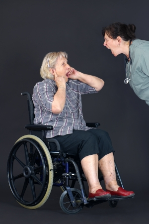 abuse: Elder abuse concept with a senior woman in a wheelchair crying and covering her ears as a middle age nurse or other health care worker is yelling at her.