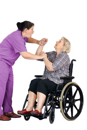 aggressive people: Elder abuse concept: enraged nurse or other healthcare provider assaulting a senior woman patient in a wheelchair, studio shot on white. Stock Photo