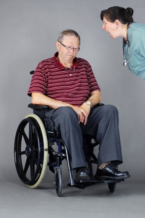 Elder abuse concept: senior man with head down in a wheelchair as a crazy nurse or other health care worker is yelling at him Stock Photo