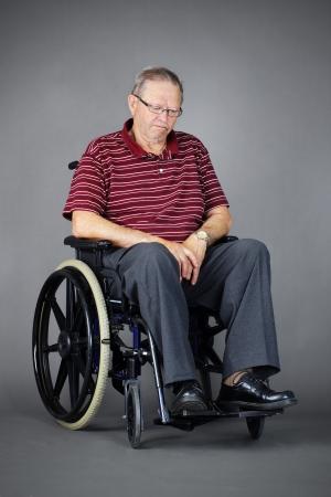 Sad or depressed senior man in a wheelchair, looking down,\ studio shot over grey background.