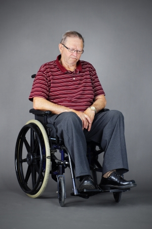grieving: Sad or depressed senior man in a wheelchair, looking down, studio shot over grey background.