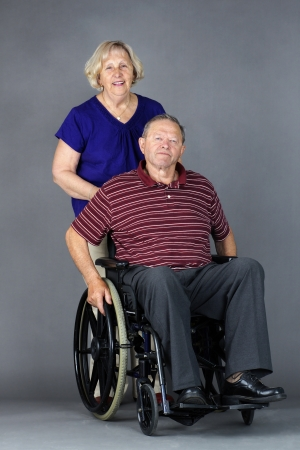 Happy senior couple with old man in a wheelchair, studio shot on grey. photo