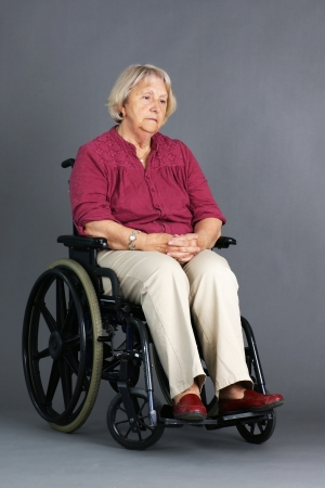 injured woman: Sad or depressed senior woman in a wheelchair, looking down, studio shot over grey background. Stock Photo