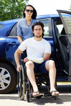 Young couple leaving or arriving to the hospital,young man in wheelchair with a cast on his hand. photo