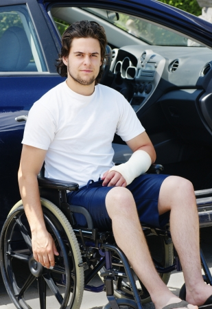 Young man with plaster cast after an accident in wheelchair arriving or leaving the hospital, car with opened door in the background. photo