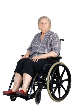 Sad or depressed senior woman in a wheelchair, looking down, studio shot isolated over white background. photo