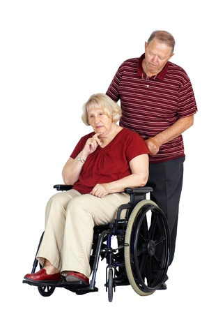 caring for: Elderly or senior couple with man caring for his wife in a wheelchair, looking sad or depressed, studio shot isolated over white background. Stock Photo