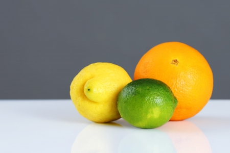 Beautiful studio still life of whole citrus fruits, orange, lemon and lime on white table and grey wall, perfect background for nutrition, diet, healthy eating, organic or other food concept.