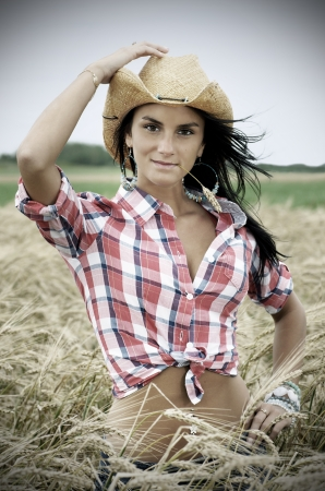 Beautiful nostalgic or vintage desaturated portrait of a friendly brunette cowgirl with cowboy hat chewing straw in a wheat field. photo